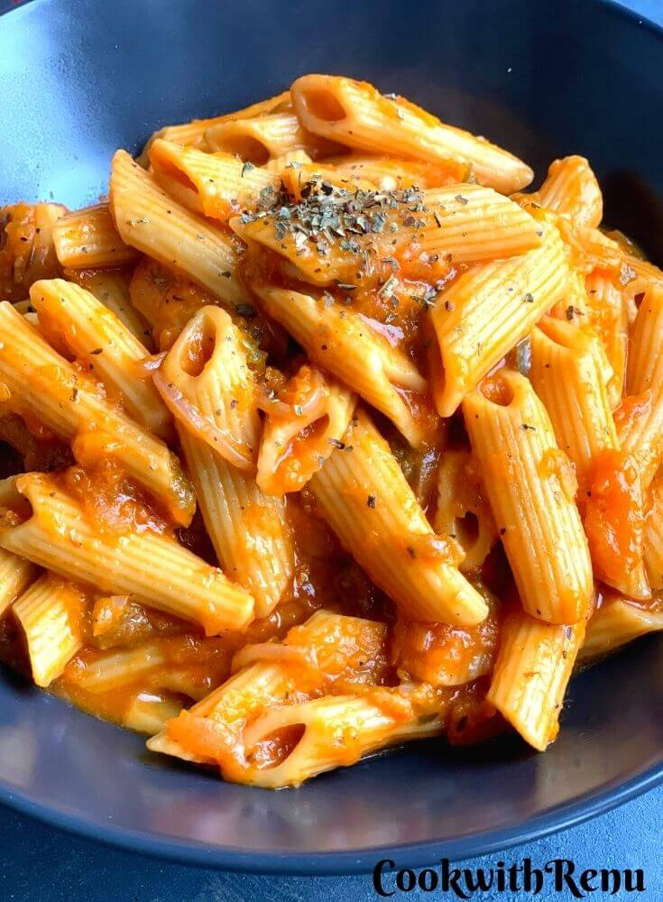 Close up look of pasta bowl served in a blue bowl.