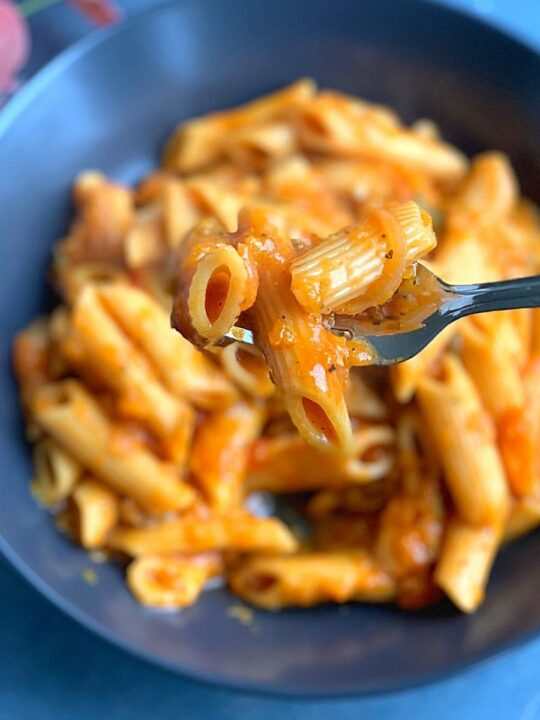 Vegan Butternut Squash Pasta is creamy and rich, one-pot cheese-free and dairy-free pasta made in an instant pot or open pot. Close up look of the pasta picked up on a fork.