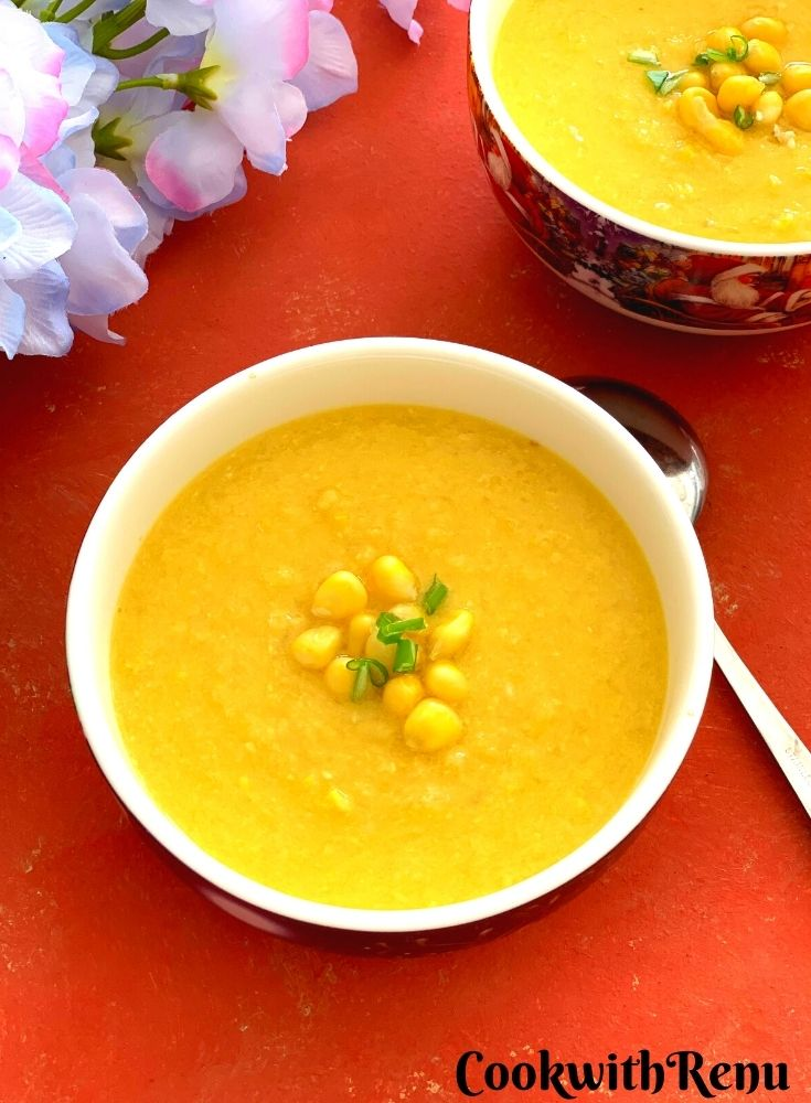 Close up look of Vegan Sweet Corn Soup served in 2 white bowl, garnished with corn kernels and few scallion greens