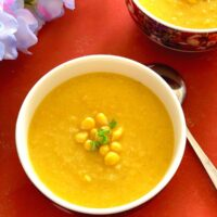 Close up look of Vegan Sweet Corn Soup served in white bowl, garnished with corn kernels and few scallion greens