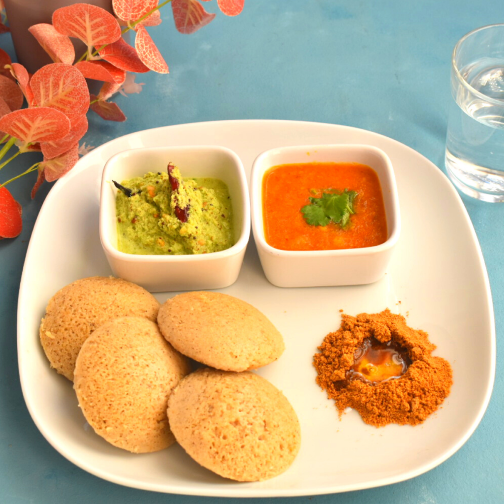 4 Idlis served along with chutney, sambar, podi with ghee on a white plate