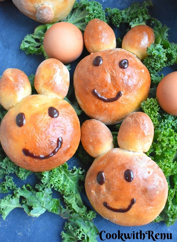 Bunny shaped buns laid on some green veggies along with eggs on the side.