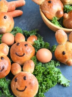 Bunny shaped buns laid on some green veggies along with eggs on the side. Also there are are more buns in the basket
