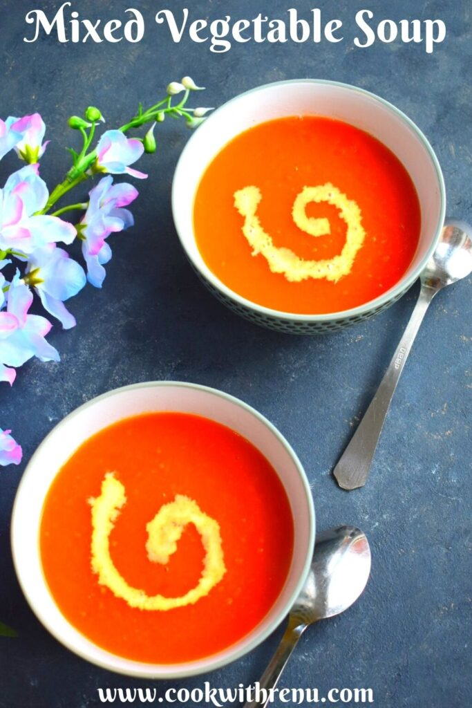 2 Bowls of Soup, with a bit of cream garnish. Seen along side are some artificial flowers