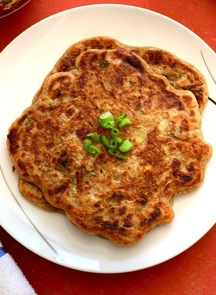 Close up look of pancakes served on a white plate with a bit of garnish of green onions