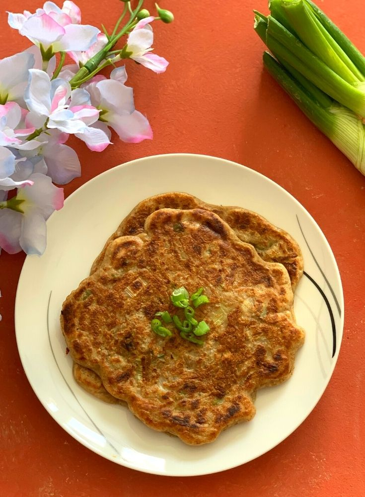 Sourdough Discard Scallion Pancakes served on a white plate. Seen on the side along with some green scallion