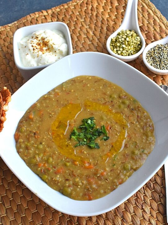 Close up view of Bajra and Green Dal Khichdi served in a white rectangular bowl, with ghee drizzled on top and some coriander sprinkled. Seen in background is dal and bajra, along with dahi and sabudana (Sago seeds) papad