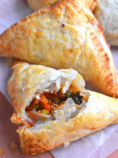 Close up look of cut puff pastry with filling seen inside. Seen in the background are few more puff lying.