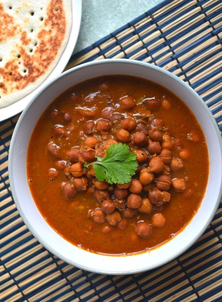 Black Chickpeas Curry Served in a bowl and seen on a blue brown placemat. Seen along are some amboli served