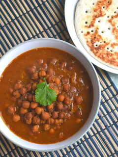 Kala Chana Served in a bowl and seen on a blue brown placemat. Seen along are some amboli served