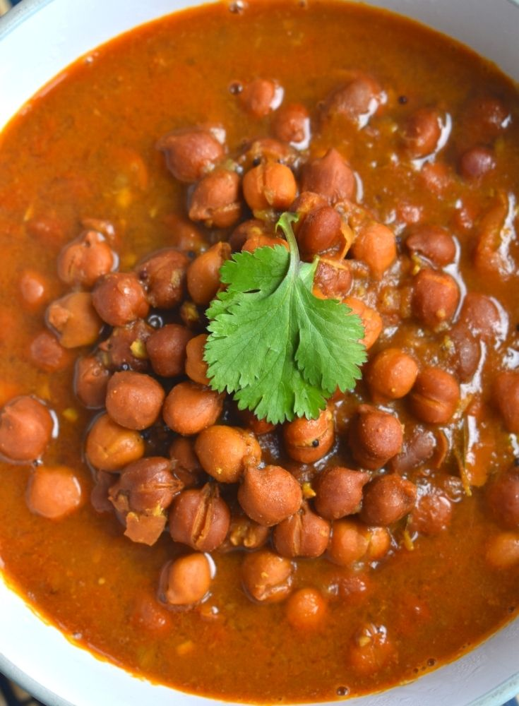 Close up look of Kala Chana Amti served in a bowl with a small coriander leaf on top. The cooked chana is visible perfectly
