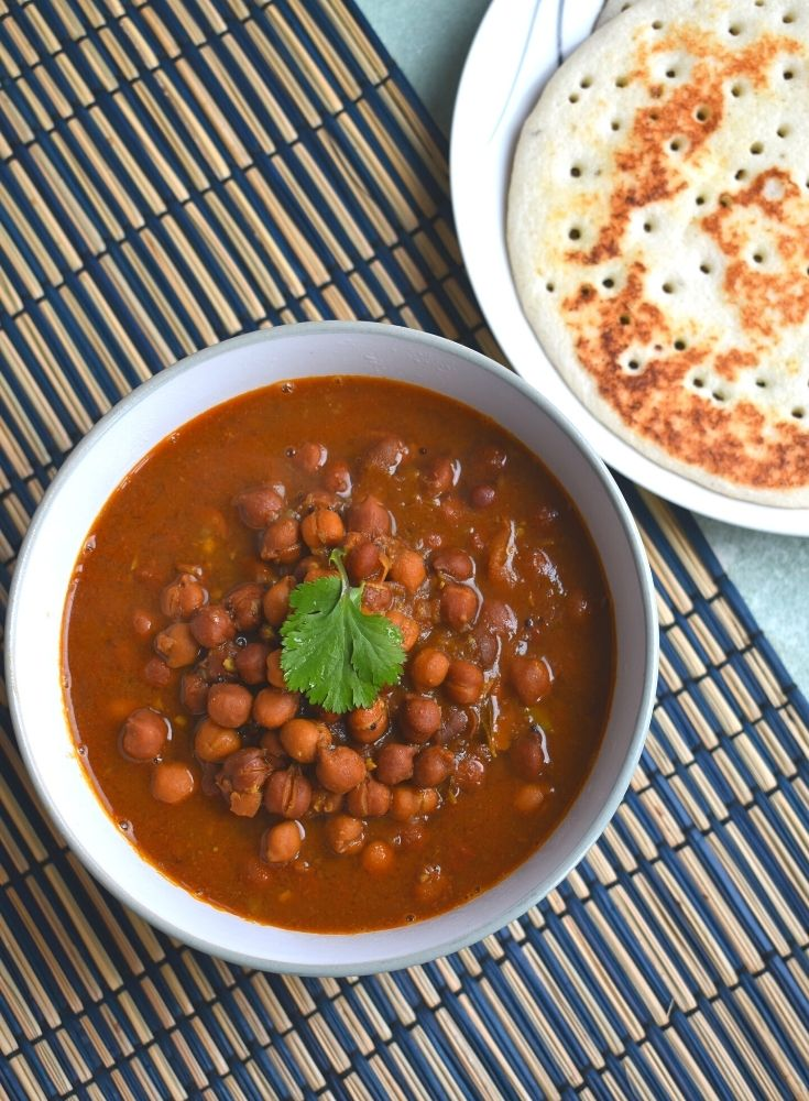 Desi Chana curry Served in a bowl and seen on a blue brown placemat. Seen along are some amboli served