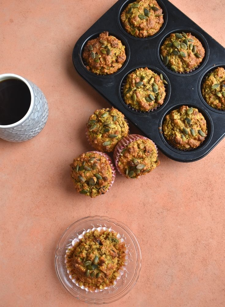 Top view of breakfast muffins on a plate and in muffin cases along with a cup of coffee