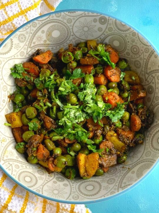 A grey bowl with the sabji and coriander garnished on top. Seen on the side is a yellow kitchen towel
