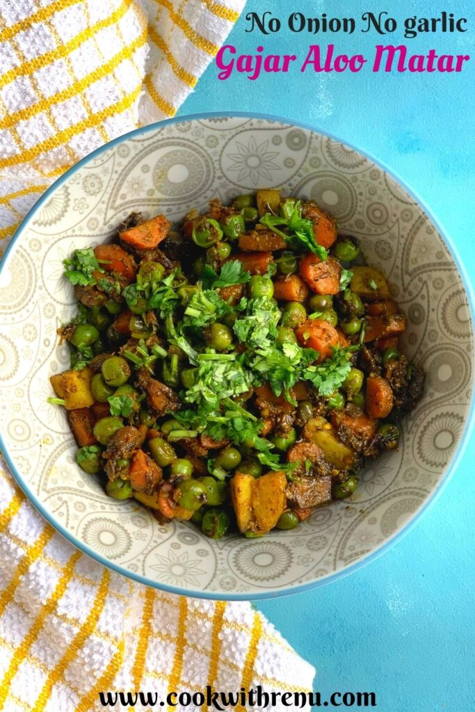 A grey bowl with Gajar Aloo Matar sabji and coriander garnished on top. Seen on the side is a yellow kitchen towel