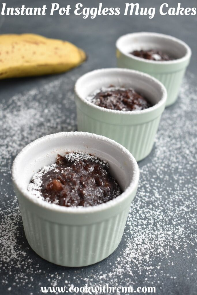 3 Chocolate Instant Pot Mug cakes seen in a line, with a banana on the side. It has a drizzle of white icing sugar