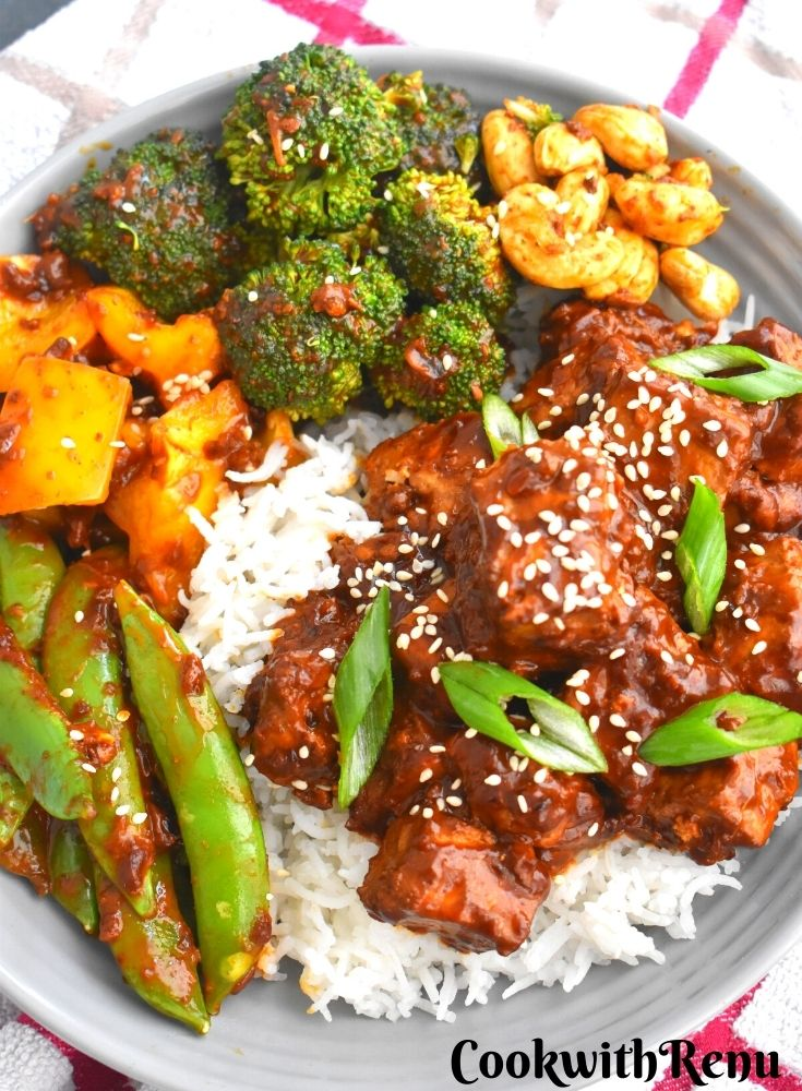 Pan-Fried Crispy Tofu served along with rice, green peas, yellow peppers, broccoli and cashew in a grey plate