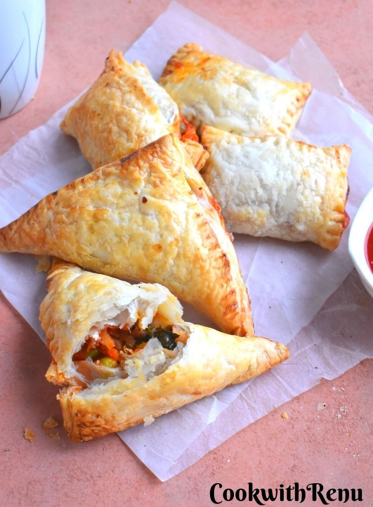 Few Veg Puff pastry seen with Tomato ketchup.