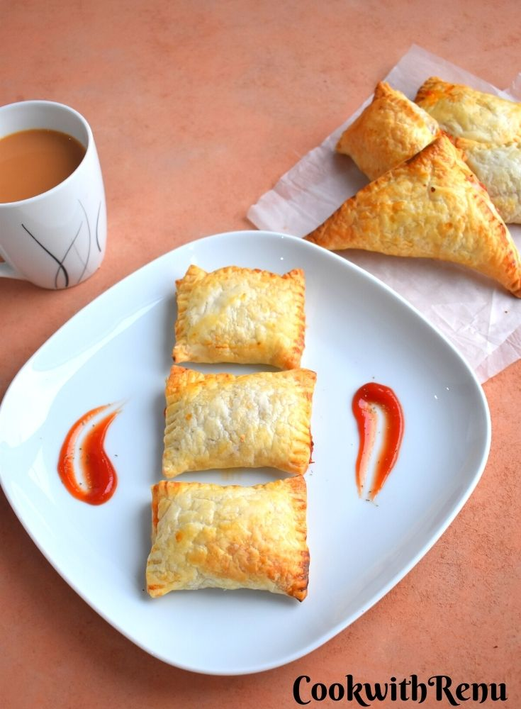 3 rectangular Veg puffs arranged on a plate, with a drizzle of tomato ketchup on the side. Few seen in the background along with a cup of tea.
