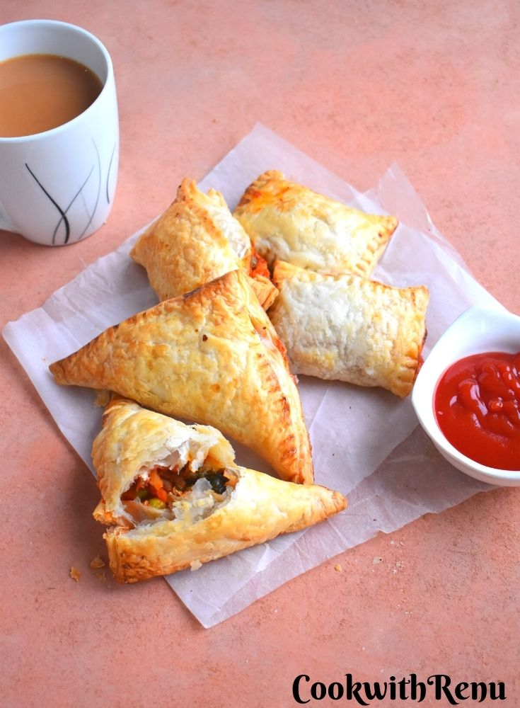 Few Veg Puff pastry seen with Tomato ketchup and tea on the side.