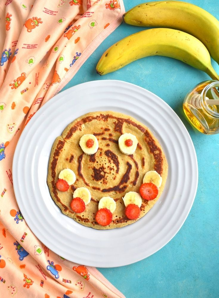 Eggless Whole Wheat Banana Pancakes with a smiley face decorated using banana and strawberries with banana and honey on the side