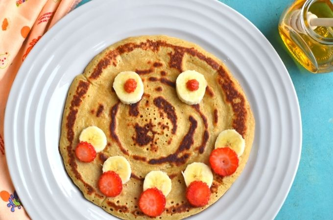 Close up look of Eggless Banana pancakes with a smiley face decorated using banana and strawberries with honey bottle on the side