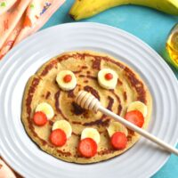 Pancake with a smiley face decorated using banana and strawberries with banana and honey on the side.