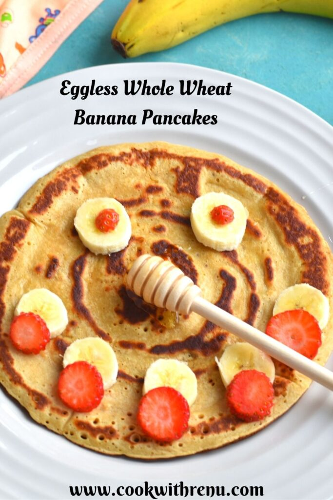 Eggless Whole Wheat Banana Pancakes with a smiley face decorated using banana and strawberries with banana seen on the side