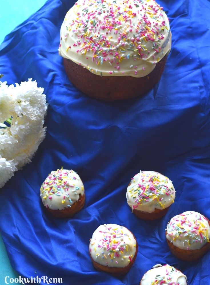 Easter Bread in round and Muffin shape, on a blue cloth with white icing and sprinkler decorations. Seen are some white flowers in the background