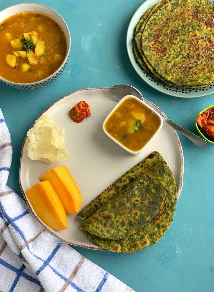 Paratha served with pickle, aloo tamatar sabji, mango and home made papad