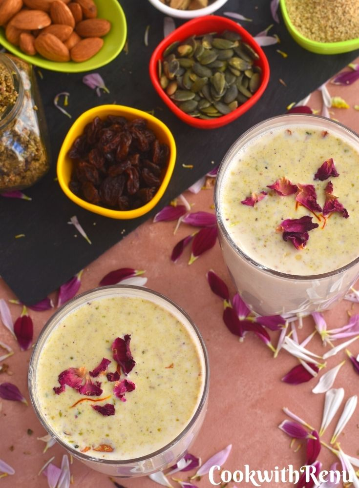 Close up look of A glass of Thandai with garnish of saffron and rose petals.