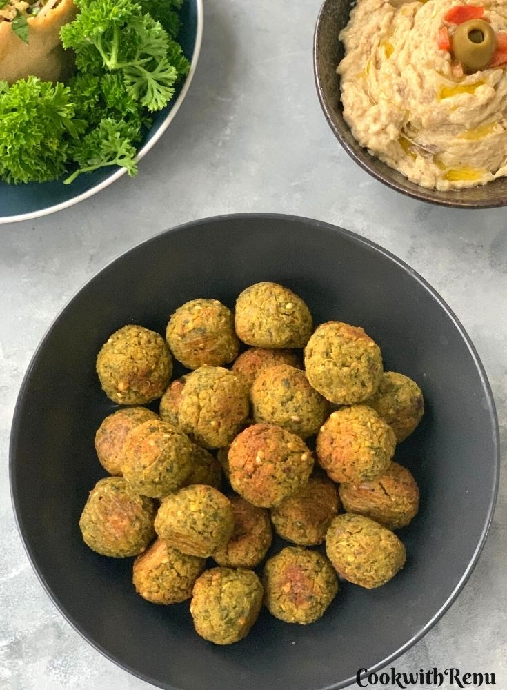 Easy Homemade Baked Falafel seen on a black plate. Seen in the background is parsley and baba ghanoush.