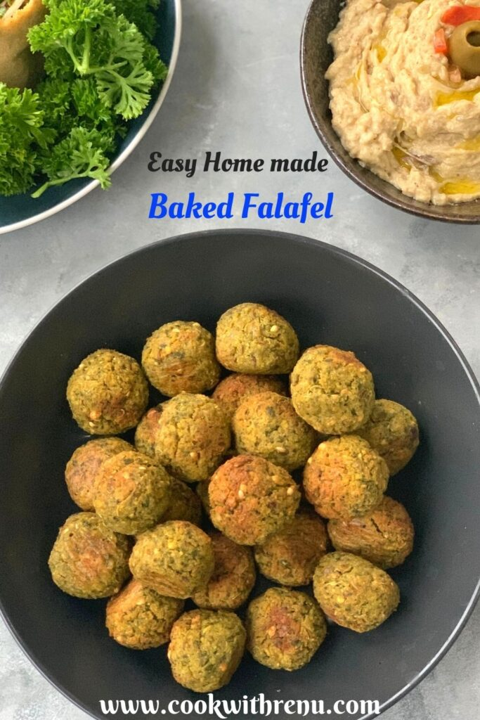 Baked Falafel seen on a black plate. Seen in the background is parsley and baba ghanoush.