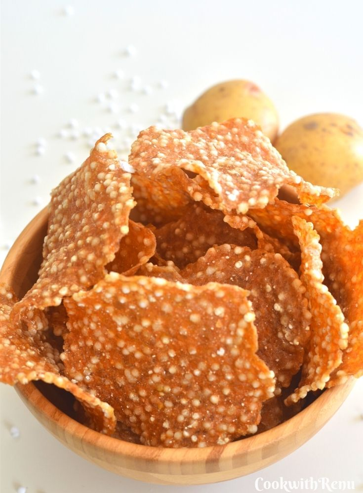 A brown bowl filled with papad and seen in the background are 2 potatoes and some sabudana