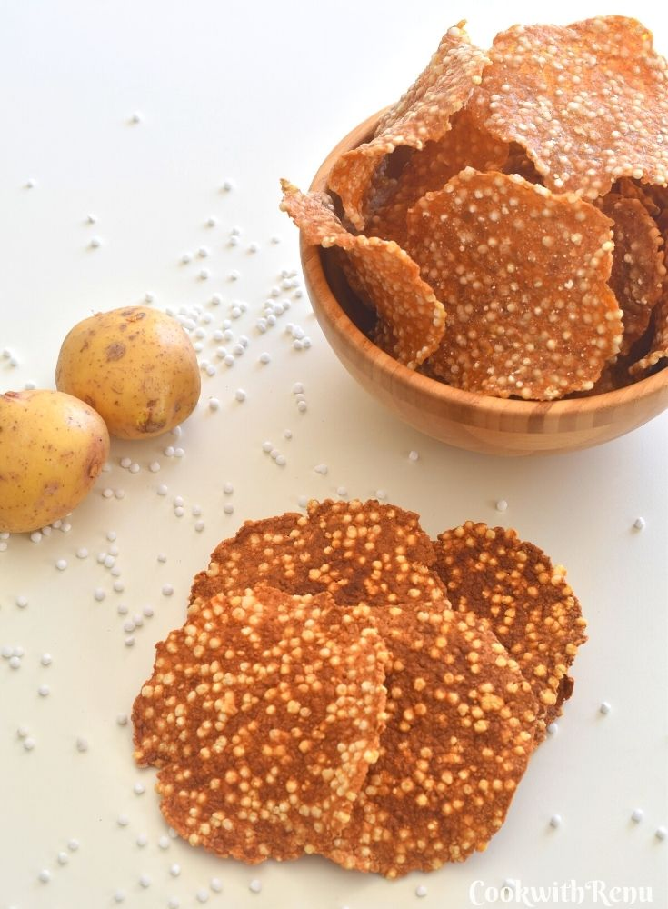 Fried papads along with uncooked papad in a brown bowl. Seen in the background are potatoes and sabdana seeds in the background