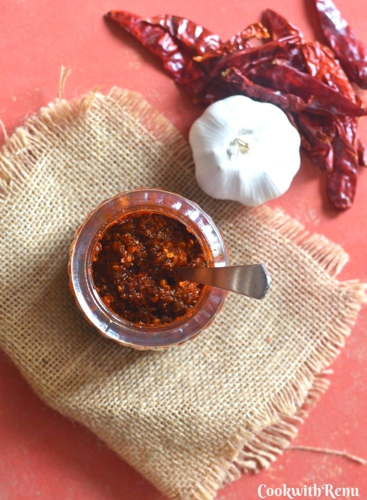 Top view of Schezwan chutney in a jar, with garlic and red chillies on the side