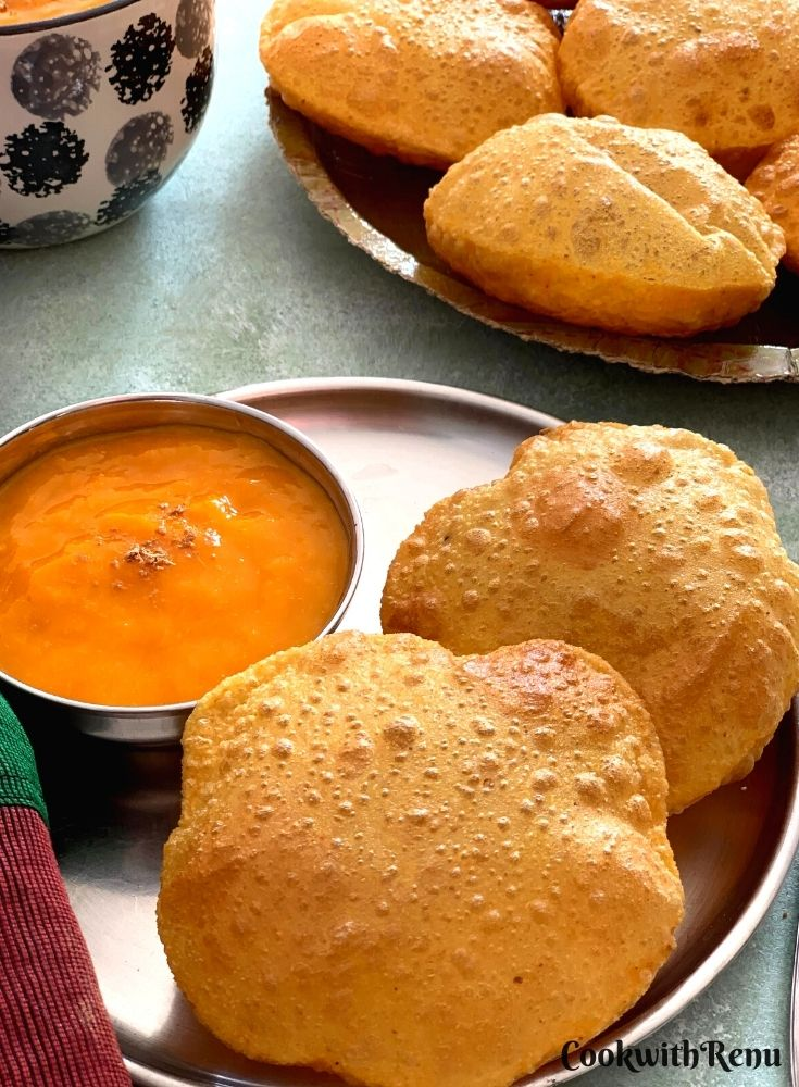Puris served with a bowl of Aamras. Few more pooris seen in the background