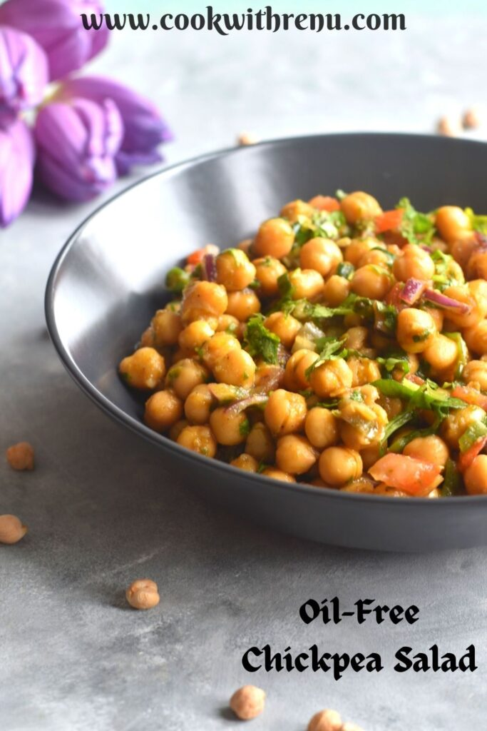 Chickpea salad served in a black bowl, with some chickpeas seen scattered with some tulips seen in the background