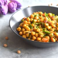 Close up look of Chickpea salad served in a black bowl, with some chickpeas seen scattered with some tulips seen in the background