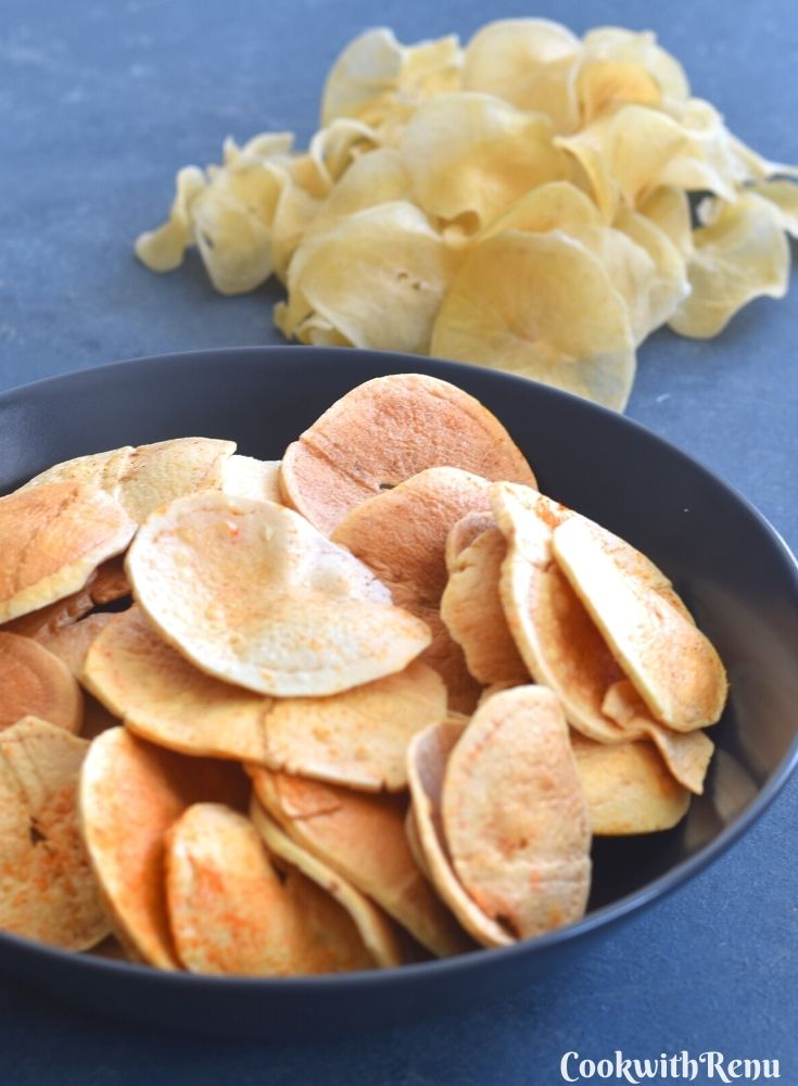 Fried Sun-Dried Potato Chips served in a blue bowl, with uncooked potato chips seen in background