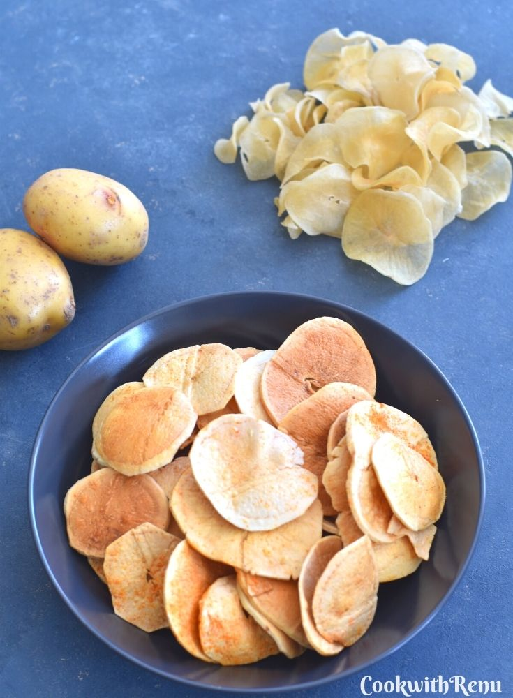 Fried Sun-Dried Potato Chips served in a blue bowl, with uncooked potato chips and 2 potatoes seen in background