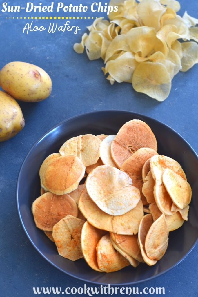 Fried Sun-Dried Potato Chips served in a blue bowl, with uncooked potato chips and 2 potatoes seen in the background
