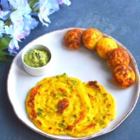 Dhuska pancake and appe served in a white dish with coconut chutney