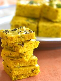 Foxtail millet dhokla stacked up and presented , seen in the background is some more dhokla served on a plate