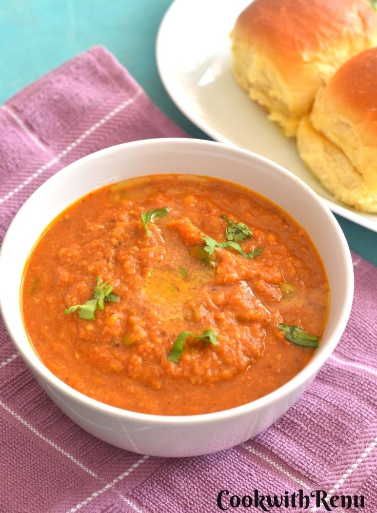Pav Bhaji being served in a white bowl. Seen along side are some pav.