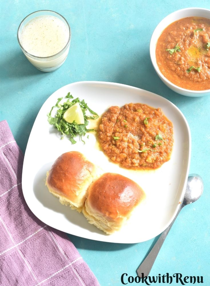 Pav Bhaji served on a white plate with 2 pav, coriander and lemon. Seen in the background is a glass of buttermilk and a bowl full of pav bhaji