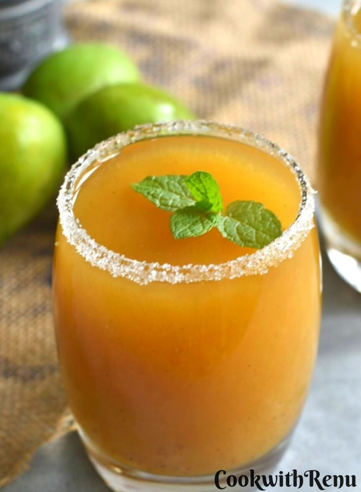 Close up view of Aam panna served in a glass with mint garnish. Seen along side are some green raw mango