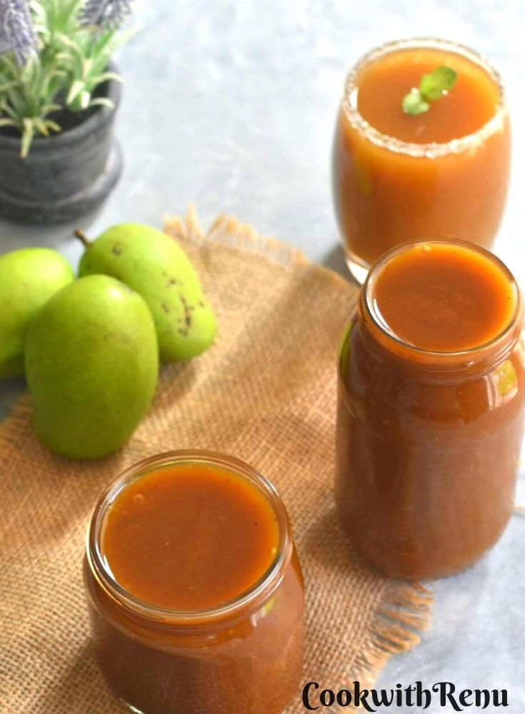 Aam panna concentrate as filled in glass jars. Also a glass made of aam panna drink with some green raw mangoes