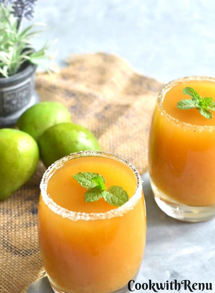 Aam Panna with Jaggery served in 2 glasses with a mint garnish. Seen along side are some green mangoes