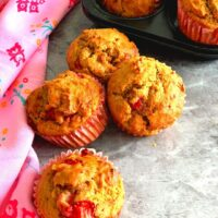 Eggless Strawberry Muffins seen on a grey table with a stole beside it